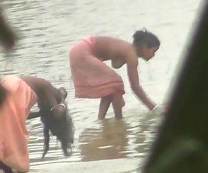 Indian women bathing by..